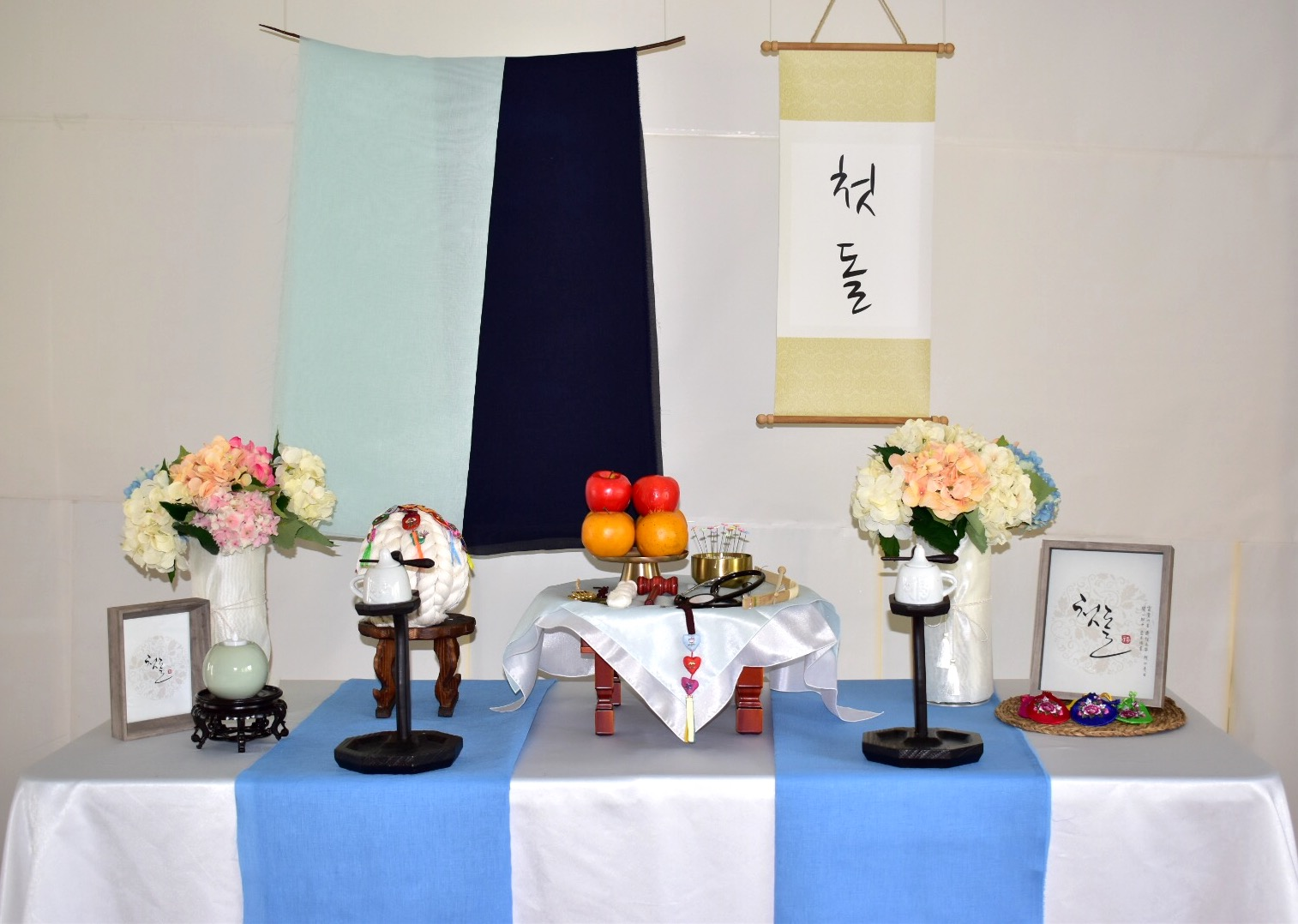 PETIT STYLE TABLE RENTAL: 하늘선비 첫돌 족자(Navy,babyblue BOard) - Included: Two tone backdrop, 1st Birthday hanging board, round wooden table, traditional tablecloth, traditional runner, small tablecloth, 2 kerosene lamps, 1 mini wooden square table, traditional candle holder, display apples, rice cakes, silk flowers and plastic vases, shil ta rae, traditional accessories are randomly picked, 2 picture frames, Doljabi Items (Pick 5 items- Ma-pae, coin, stethoscope, writing brush, thread, bow and arrow)** Mix &Match backdrops and runners (choose from traditional table)*** Pick up- Everything included in the picture except display rice cakes, display fruits, brass plates.* Out of state - mini wooden table, display rice cakes, apples are not included. (optional). All accessories are randomly picked.*Shipping fee will apply. Fees might vary depending on location.상품구성: 투톤 행인 러너, 족자, 고급, 한복 원단 러너,상보, 호롱불 촛대 2개, 호롱불 2개,전통 사각 소반 1개, 전통 촛대 1개, 모형 사과, 백설기, 꽃과 플라스틱병 2개, 플라스틱 꽃병 2개, 상화, 실타래, 전통 장식품들 랜덤, 액자 2개, 돌잡이 용품(5개 선택 - 활, 실, 엽전, 마패,붓, 청진기)** Traditional Table 에서 현수막, 러너 Mix & Match 하실수 있습니다.* Pick up- 사진에 모든 물품 포함되지만 모형떡, 과일, 유기그릇은 포함되지 않습니다. 전통 소품들은 랜덤입니다.* 타주시- 깨지지 않은 소품들로 나갑니다. 유기그릇, 개다리 소반은 포함되지 않으며, 모형 과일, 떡은 옵션입니다. 전통 소품들은 랜덤입니다.* 배송시 배송비는 추가이며, 지역따라 배송비가 다를수 있습니다.