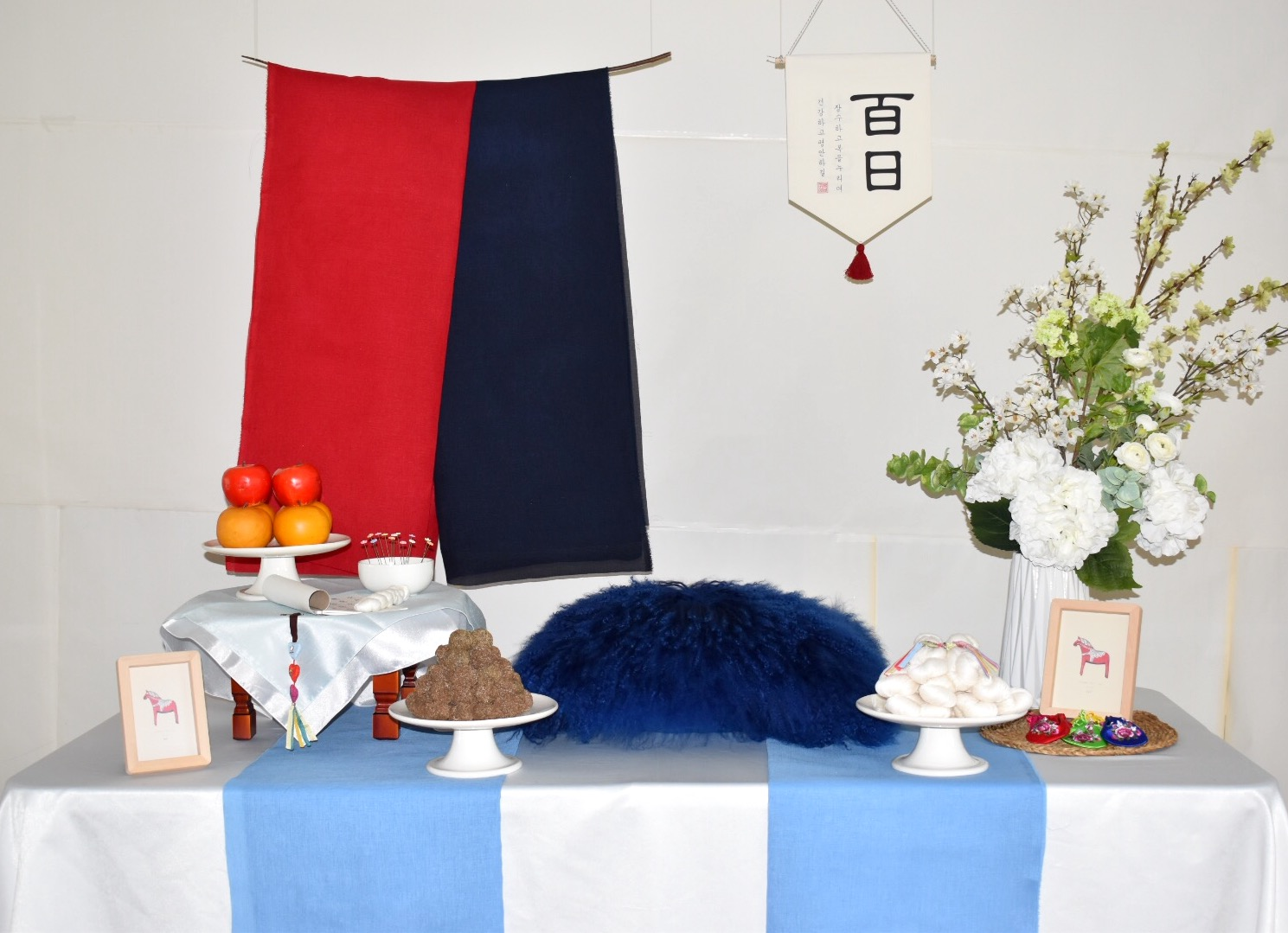 PETIT STYLE TABLE RENTAL: 태극 백일 (The First red-Navy) - Included: Two tone hanging runner, round wooden table, traditional tablecloth, traditional runner, small tablecloth, display fruits(option), rice cakes(option), silk flowers and plastic vases, shil ta rae, traditional accessories are randomly picked, 2 picture frame** Mix &Match backdrops and runners *** Pick up- Everything included in the picture except display rice cakes, display fruits, cushion.* Out of state - display rice cakes, apples are not included. (optional).* Shipping fee will apply. Fees might vary depending on location.상품구성: 투톤 행인 러너 2개, 상 1개, 한복 원단 러너,상보, 모형 과일(옵션), 모형 떡(옵션), 꽃과 아크릴 화병, 상화, 실타래, 전통 장식품들 램덤, 액자 2개** 러너 Mix & Match 하실수 있습니다.*** Pick up- 사진에 모든 물품 포함되지만 모형떡, 과일, 방석은 포함되지 않습니다. 전통 소품들은 랜덤입니다.* 타주시 - 깨지지 않는 소품들로 나갑니다. 모형 과일, 떡은 옵션입니다. 전통 장식품들은 랜덤입니다.*배송시 배송비는 추가이며, 지역따라 배송비가 다를수 있습니다.