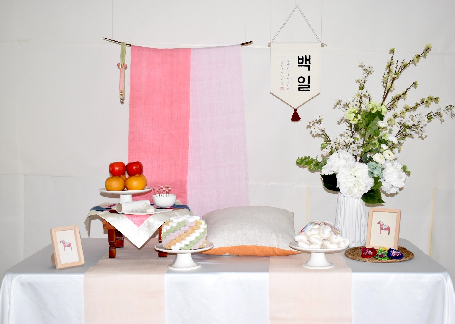 PETIT STYLE TABLE RENTAL: 핑키밍키 백일(Pinky minky) - Included: Two tone hanging runner, round wooden table, traditional tablecloth, traditional runner, small tablecloth, display fruits(option), rice cakes(option), silk flowers and plastic vases, shil ta rae, traditional accessories are randomly picked, 2 picture frame** Mix &Match backdrops and runners *** Pick up- Everything included in the picture except display rice cakes, display fruits, cushion.* Out of state - display rice cakes, apples are not included. (optional).* Shipping fee will apply. Fees might vary depending on location.상품구성: 투톤 행인 러너 2개, 상 1개, 한복 원단 러너,상보, 모형 과일(옵션), 모형 떡(옵션), 꽃과 아크릴 화병, 상화, 실타래, 전통 장식품들 램덤, 액자 2개** 러너 Mix & Match 하실수 있습니다.*** Pick up- 사진에 모든 물품 포함되지만 모형떡, 과일, 방석은 포함되지 않습니다. 전통 소품들은 랜덤입니다.* 타주시 - 깨지지 않는 소품들로 나갑니다. 모형 과일, 떡은 옵션입니다. 전통 장식품들은 랜덤입니다.*배송시 배송비는 추가이며, 지역따라 배송비가 다를수 있습니다.