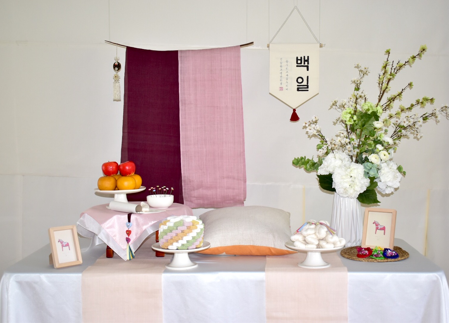 PETIT STYLE TABLE RENTAL:딥핑크 백일(DEEP PINK) - Included: Two tone hanging runner, round wooden table, traditional tablecloth, traditional runner, small tablecloth, display fruits(option), rice cakes(option), silk flowers and plastic vases, shil ta rae, traditional accessories are randomly picked, 2 picture frame** Mix &Match backdrops and runners *** Pick up- Everything included in the picture except display rice cakes, display fruits, cushion.* Out of state - display rice cakes, apples are not included. (optional).* Shipping fee will apply. Fees might vary depending on location.상품구성: 투톤 행인 러너 2개, 상 1개, 한복 원단 러너,상보, 모형 과일(옵션), 모형 떡(옵션), 꽃과 아크릴 화병, 상화, 실타래, 전통 장식품들 램덤, 액자 2개** 러너 Mix & Match 하실수 있습니다.*** Pick up- 사진에 모든 물품 포함되지만 모형떡, 과일, 방석은 포함되지 않습니다. 전통 소품들은 랜덤입니다.* 타주시 - 깨지지 않는 소품들로 나갑니다. 모형 과일, 떡은 옵션입니다. 전통 장식품들은 랜덤입니다.*배송시 배송비는 추가이며, 지역따라 배송비가 다를수 있습니다.