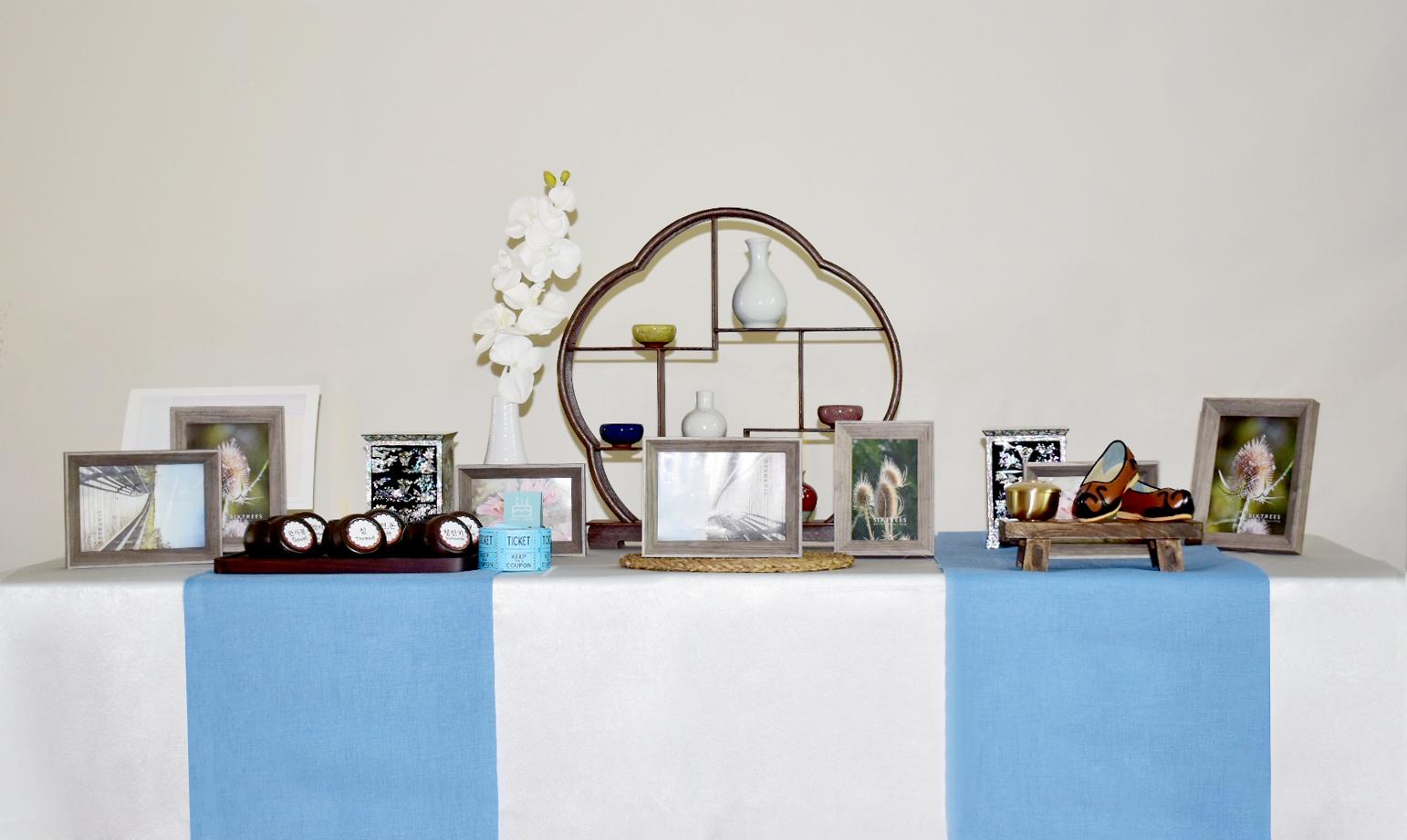Traditional photo table #2 - Included: Traditional accessories rack, 4 picture frames(5x7), 2 picture frames(4x6), traditional drawers, traditional shoes, 6 Doljabi traditional jars, mini wooden tray, flowers and vase.상품구성: 전통 장식장, 액자 5x7 4개, 액자 4x6 2개, 전통 화병과 찻잔, 전통 신발, 돌잡이 항아리6개, 모시 러너, 방짜유기 미니 밥그릇, 목화와 꽃병.