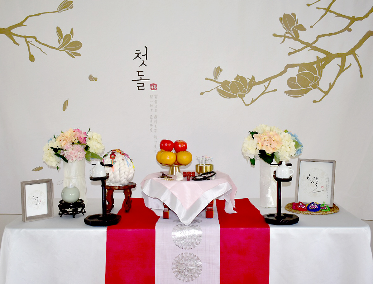 PETIT STYLE TABLE RENTAL: 장미빛 (The real rose) - Included: The Real Rose backdrop, round wooden table, traditional tablecloth, traditional runner, small tablecloth, 2 kerosene lamps, 1 mini wooden square table, traditional candle holder, display apples, rice cakes, silk flowers and plastic vases, shil ta rae, traditional accessories are randomly picked, 2 picture frames, Doljabi Items (Pick 5 items- Ma-pae, coin, stethoscope, writing brush, thread, bow and arrow)** Mix &Match backdrops and runners (choose from traditional table)*** Pick up- Everything included in the picture except display rice cakes, display fruits, brass plates.* Out of state - mini wooden table, display rice cakes, apples are not included. (optional) Will change to 2 small picture frames. All accessories are randomly picked.*Shipping fee will apply. Fees might vary depending on location.상품구성: 현수막, 상 1개, 고급 한복 원단 테이블보, 한복 원단 러너,상보, 호롱불 촛대 2개, 호롱불 2개,전통 사각 소반 1개, 전통 촛대 1개, 모형 사과, 백설기, 꽃과 플라스틱병 2개, 조화, 상화, 실타래, 전통 장식품들 랜덤, 액자 2개, 돌잡이 용품(5개 선택 - 활, 실, 엽전, 마패,붓, 청진기)** Traditional Table 에서 현수막, 러너 Mix & Match 하실수 있습니다.* Pick up- 사진에 모든 물품 포함되지만 모형떡, 과일, 유기그릇은 포함되지 않습니다. 전통 소품들은 랜덤입니다.* 타주시- 깨지지 않은 소품들로 나갑니다. 유기그릇, 개다리 소반은 포함되지 않으며, 모형 과일, 떡은 옵션입니다. 전통 소품들은 랜덤입니다.* 배송시 배송비는 추가이며, 지역따라 배송비가 다를수 있습니다.