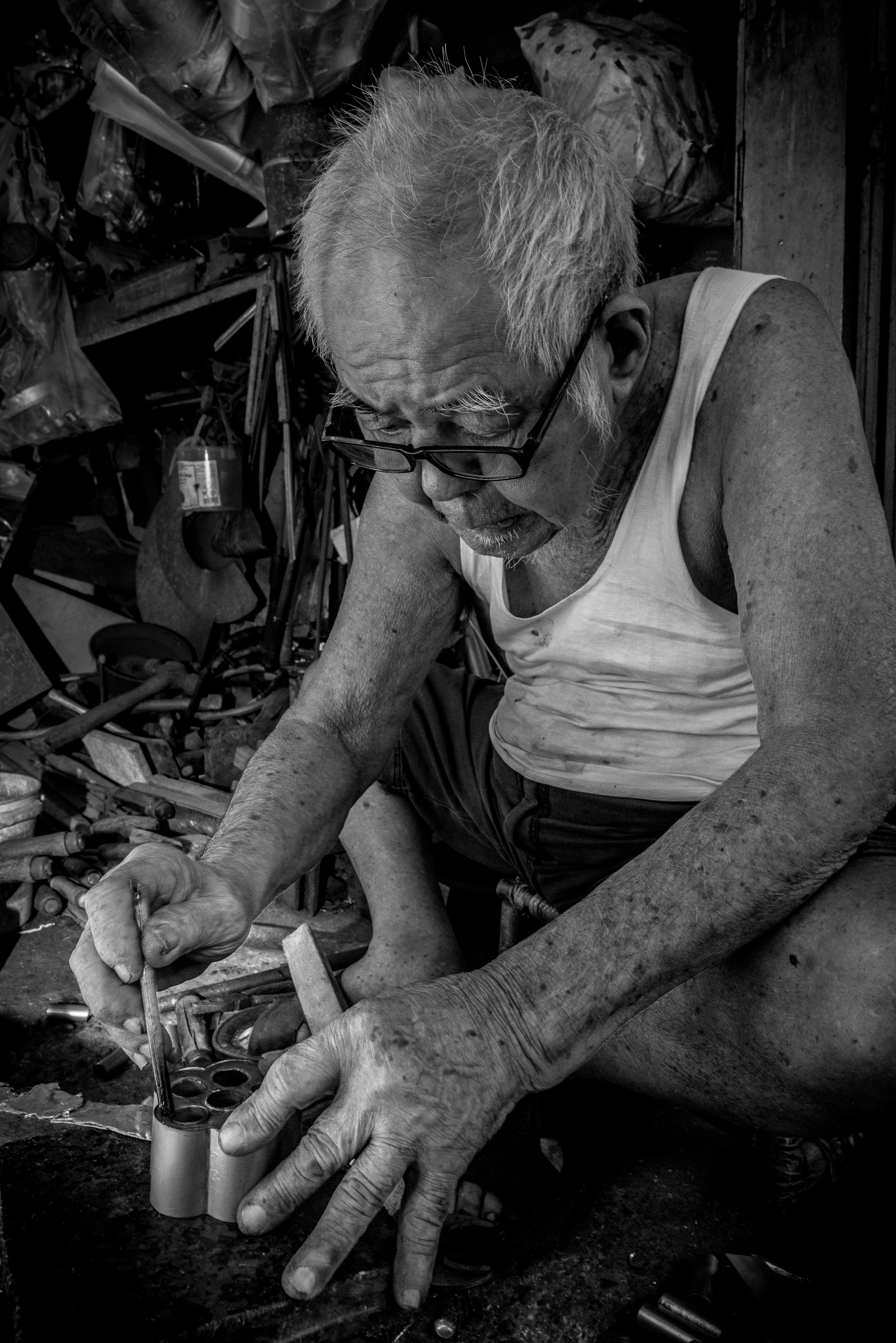 An old man making kitchenware in Kuching, Malaysia