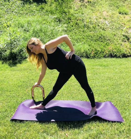"""TRIKONASANA (Triangle Pose):  Stand in a wide-legged stance. Turn your front toes to 12 o'clock Turn your back toes to 10 o'clock (left foot) or 2 o'clock (right foot). Bring your arms to a """"T"""" holding the Ubarre at the curve. While keeping both legs straight, reach your front hand (with the barre)away from you and tilt down until the Ubarre reaches the ground. Bring your back hand to your hip. (Switch sides)."""