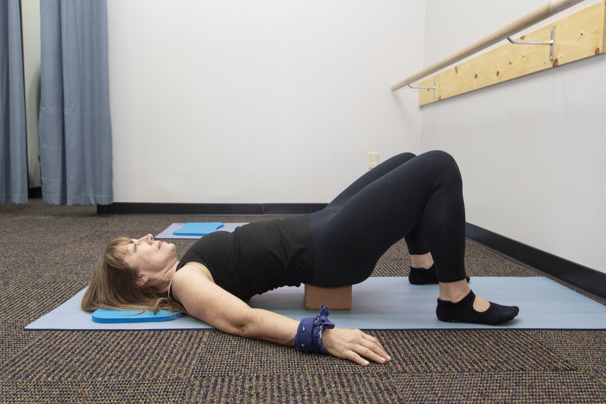 Use a block or stack of books to elongate the lumbar spine with this stretch.