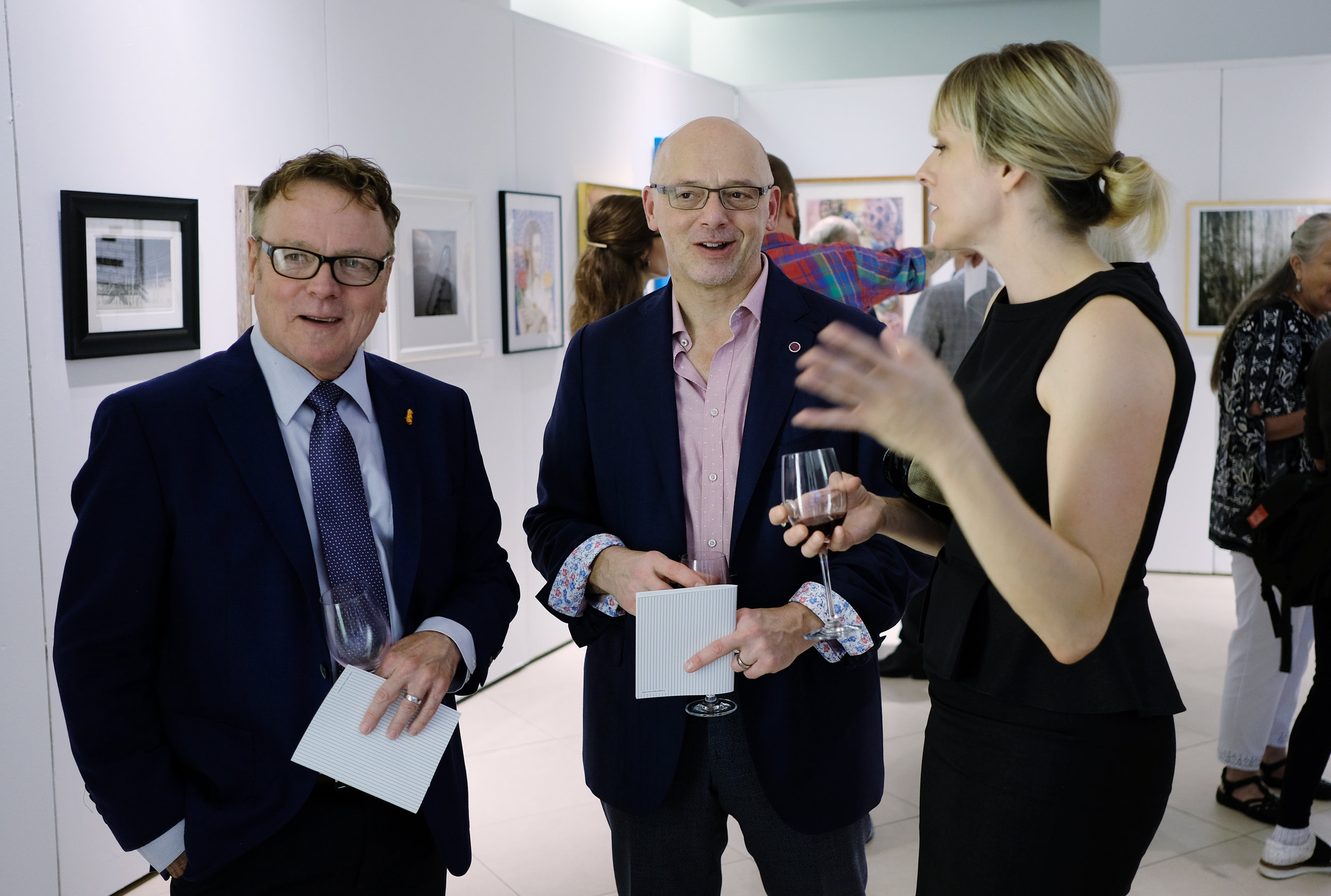 Paul Ford, Left to right, Jerry Morosco and artist Brenda Stumpf look at art at The preview opening of the 106th Annual of the Associated Artists of Pittsburgh at the SouthSide Works, September 13, 2018. Photo by Bill Wade.