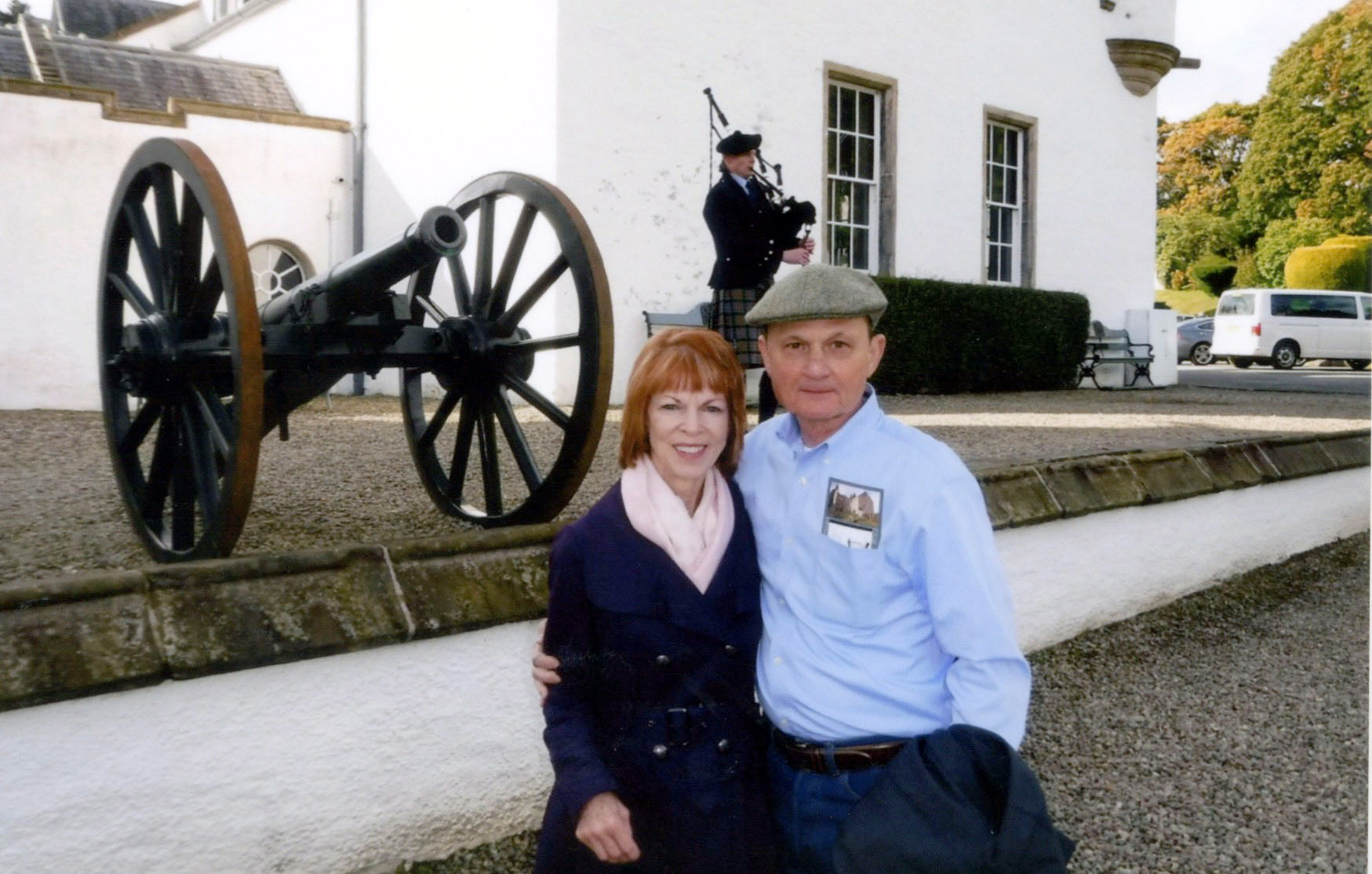 ^Carolyn and Jim stand outside of Blair Castle in Scotland while listening to the bagpiper in September 2016.