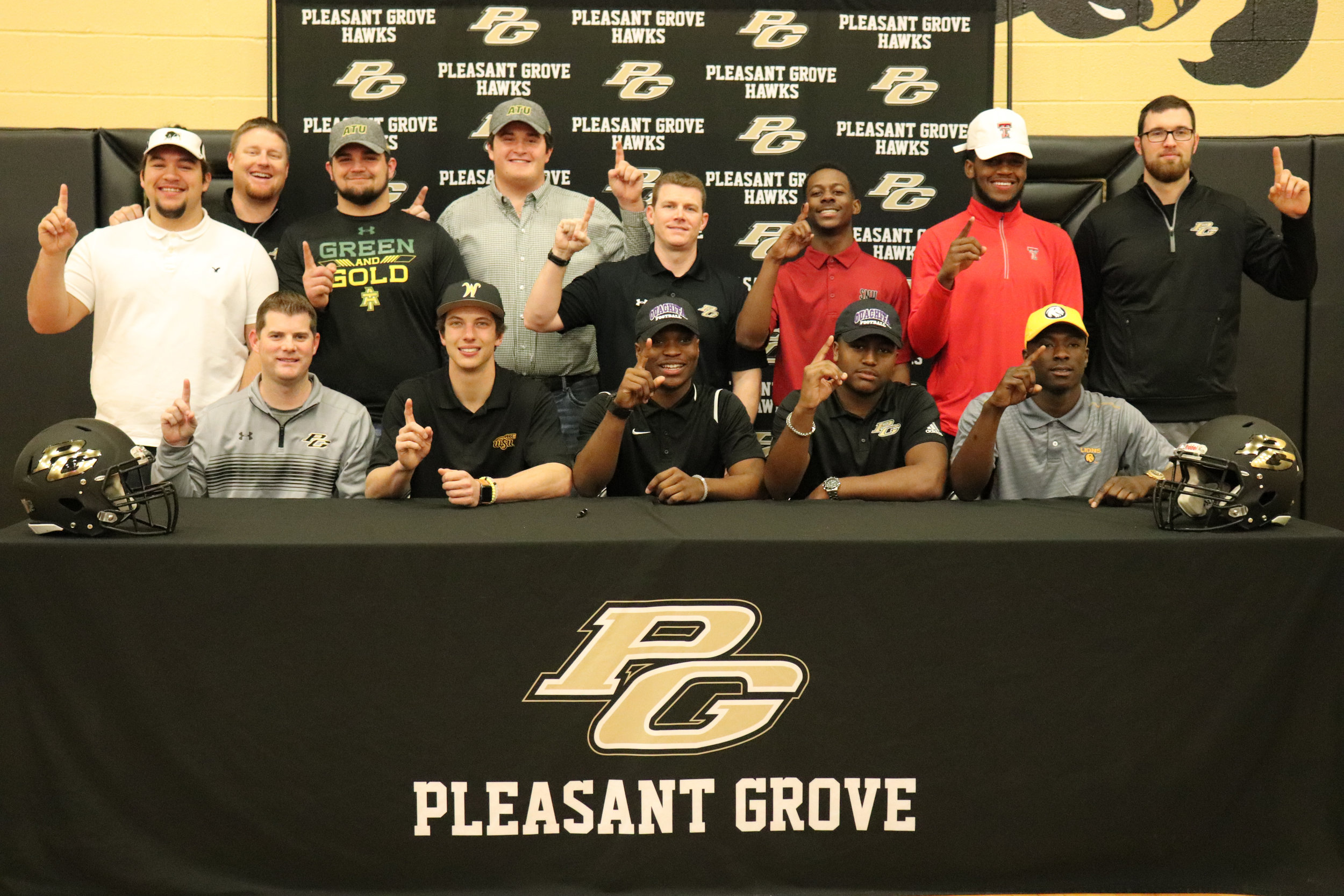 ^ During National Signing Day, nine members of the Pleasant Grove Hawk team received college scholarships which is a school record. Pictured are: (bottom row) Coach Justin Gibson, Carson Cox, TJ Cole, Caleb Porchia and Chauncey Martin; (standing) Austin Toler, Coach Riley Fincher, Nick Gavriel, Drake Fowler, Coach Josh Gibson, Cameron Wells, Xavier Benson and Coach Blake Thomas.
