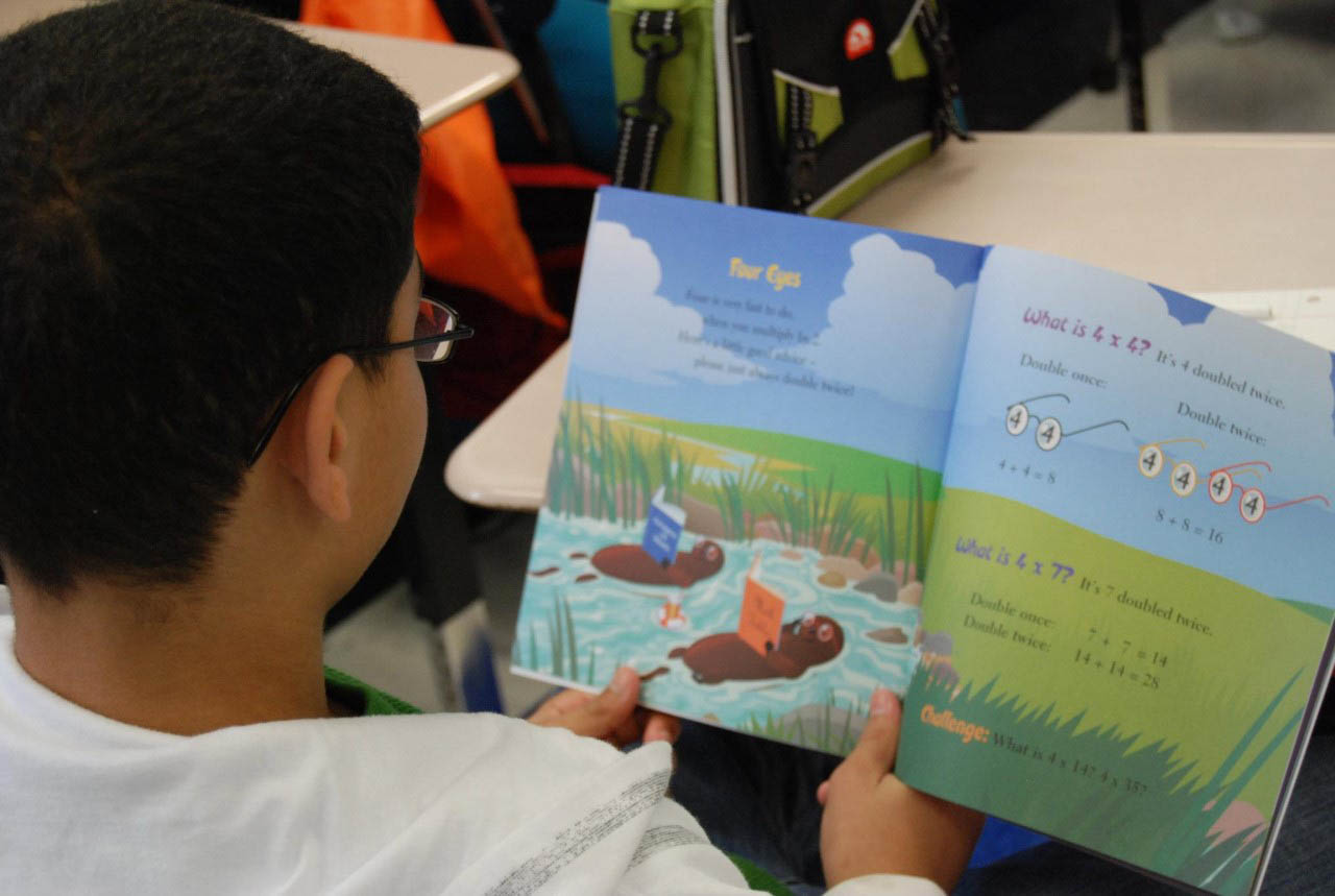 ^  A student reads a book he received during Spring into Reading, a program the Junior League of Texarkana created to encourage school-aged children to develop a greater interest in reading and to promote literacy.