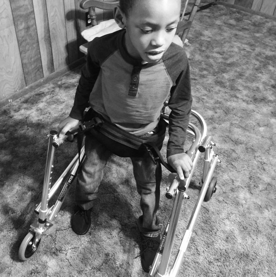 Trinton maneuvers around the house in his first walker which is used for gait training.