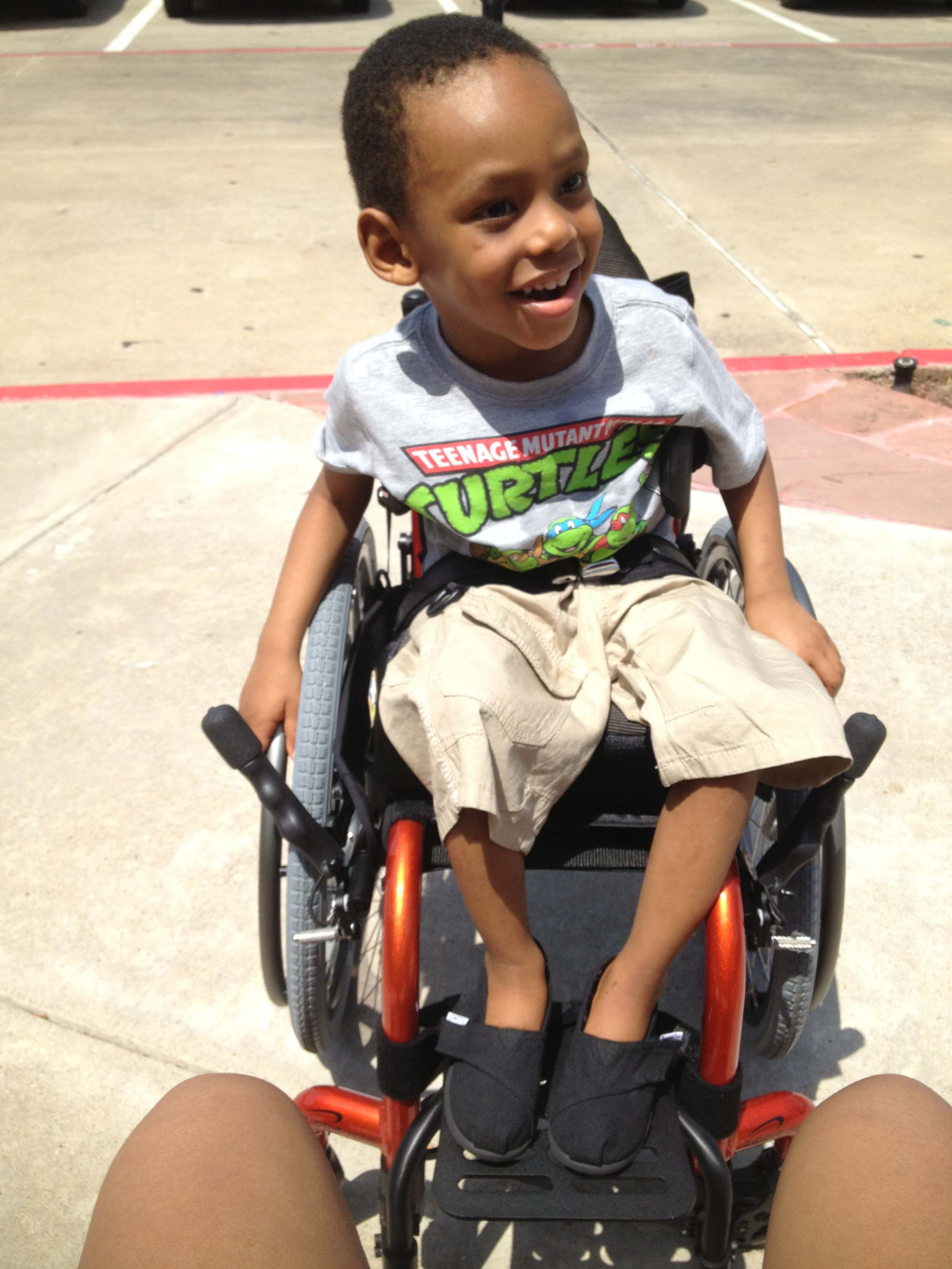 In July 2013, Trinton enjoyed being completely mobile while taking a ride in his first wheelchair.