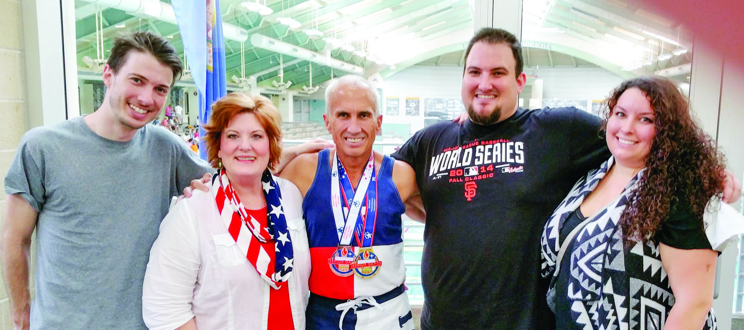 Lee received much family support during Minnesota's National Senior Games in 2015 when he won a gold medal in the 200 yd. breaststroke and a bronze in the 100 yd. breaststroke. Congratulating him are his son, Burkelee; wife, Ginger; and son, Samuel; and daughter-in-law, Anna.