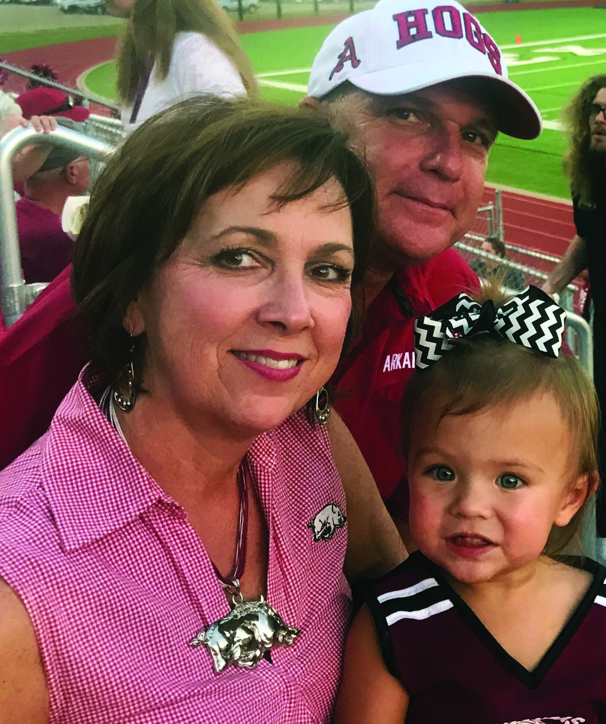 Shelby and Allen with their granddaughter, Sutton, during an Arkansas High football game.