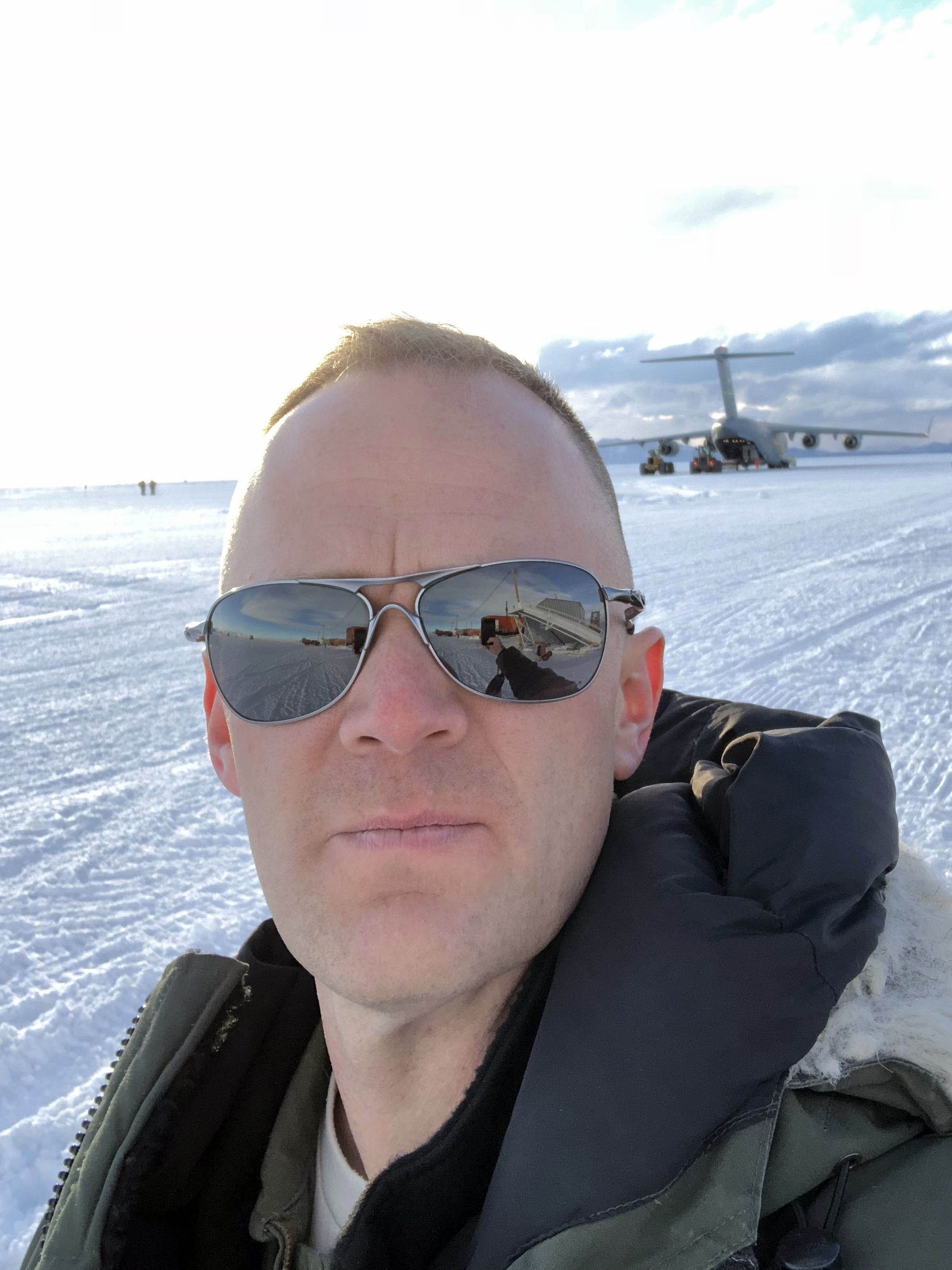 Matt stands on the flightline, 12 miles outside of McMurdo Station. In order to get there, people have to drive over sea ice onto a glacier. Pictured in the background is a USAF C-17.