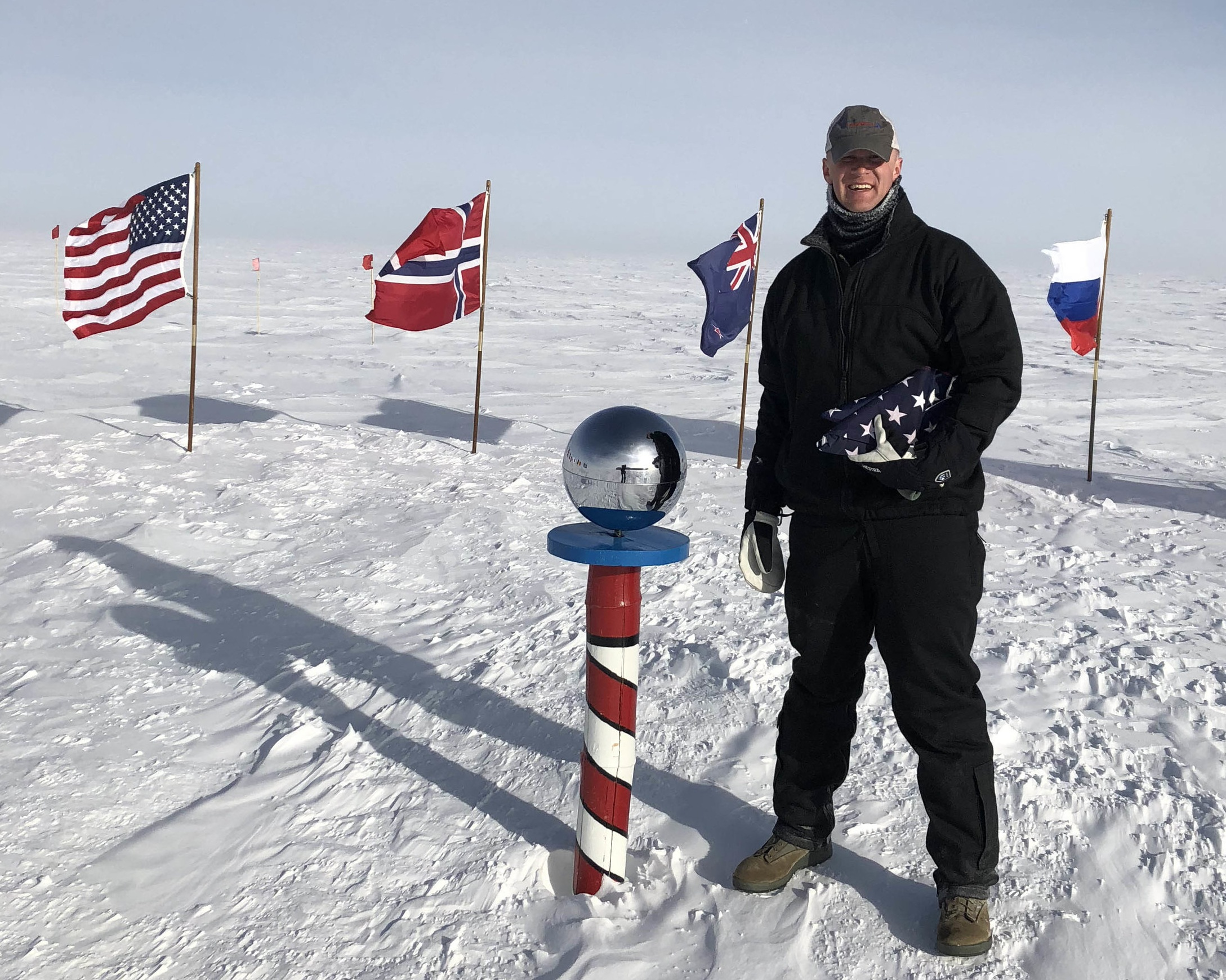 Matt at the South Pole preparing to aeromedically evacuate a patient who had high altitude pulmonary edema (HAPE) and was not stable enough to stay at South Pole Station. He is holding the American Flag that he flies in the backs of the aircraft in which he moves patients. This flag has traveled over the skies of southwest Asia, north Africa, South America, North America, the islands of the Pacific and Antarctica.