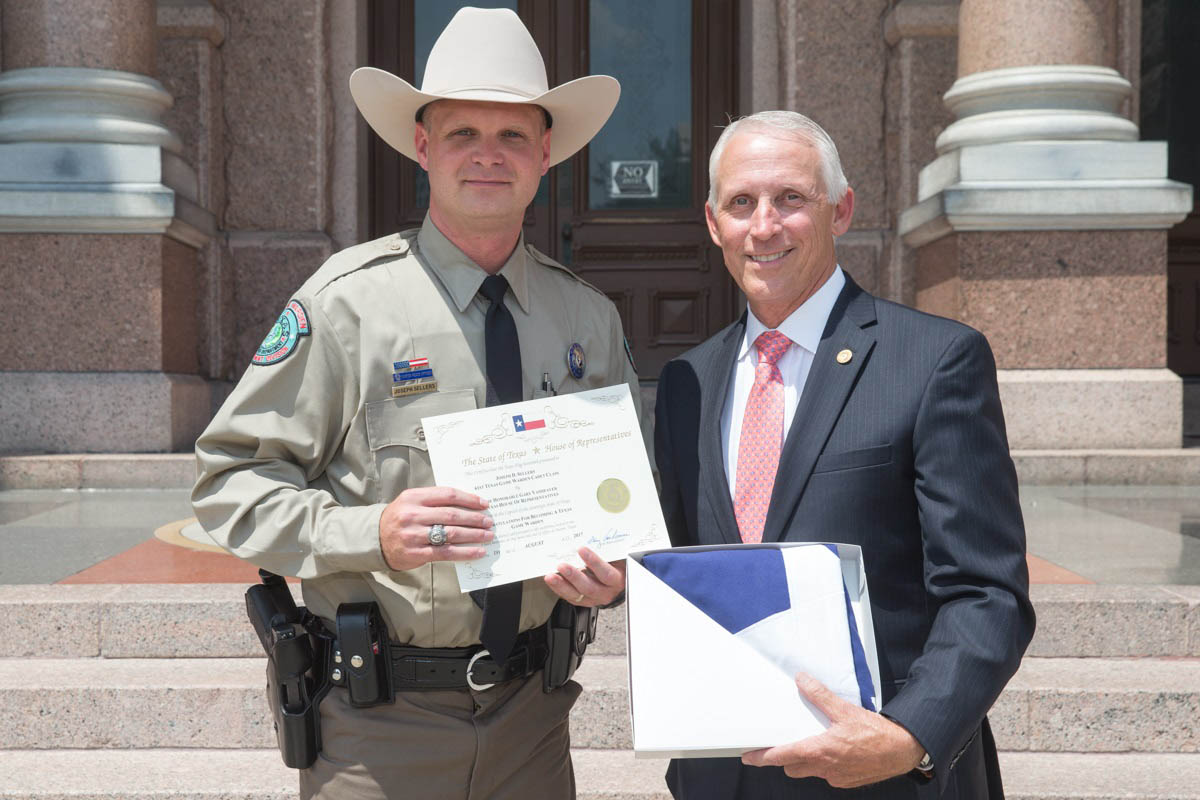 Rep. VanDeaver presents Joseph Sellers with a Texas flag flown over the Capitol in honor of Joseph becoming a Texas Game Warden in August 2017.