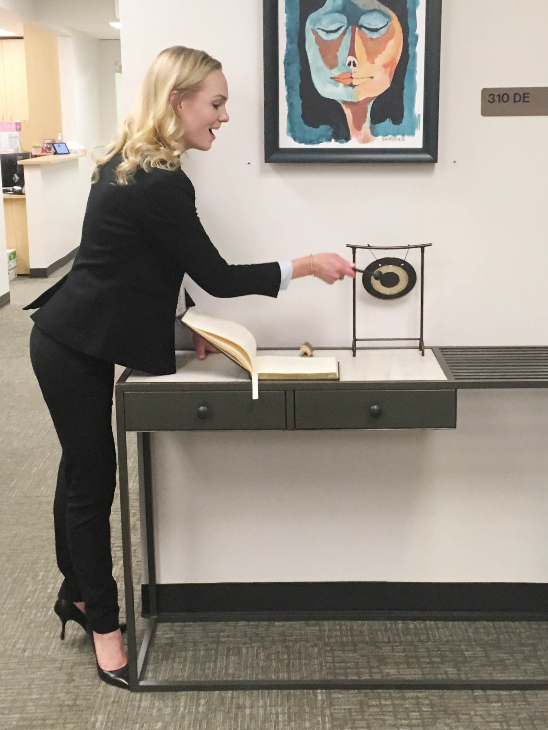 Hadley hits the celebratory gong in the Center for Medical Ethics and Health Policy at Baylor College of Medicine after successfully defending her dissertation.