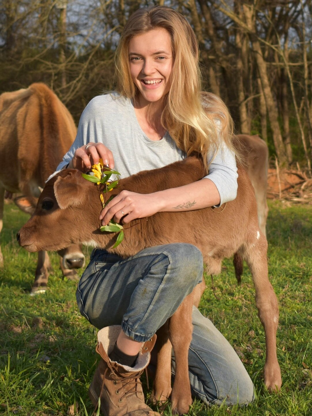 Annemarie checks on a new baby from one of her Jersey cows, known for their delicious milk (used for her personal use).