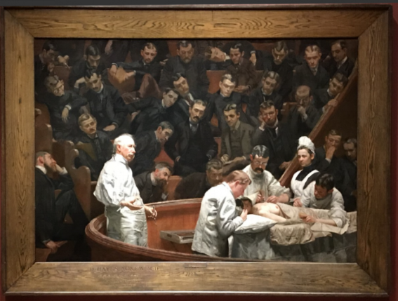 """The Agnew Clinic depicts Dr. Agnew performing a partial mastectomy in a medical amphitheater.  He stands in the left foreground, holding a scalpel.  Also present are Dr. J. William White, applying a bandage to the patient; Dr. Joseph Leidy (nephew of paleontologist Joseph Leidy), taking the patient's pulse; and Dr. Ellwood R. Kirby, administering anesthetic.    In the background, the operating room nurse, Mary Clymer, and University of Pennsylvania medical school students observe.  Eakins placed himself in the painting – he is the rightmost of the pair behind the nurse – although the actual painting of him is attributed to his wife, Susan Macdowell Eakins.   The painting, also, records the significant transition, in just 14 years, from the earlier status quo – the participants' black frock coats represented in The Gross Clinic (1875) – to the """"white coats"""" of 1889.  The painting is Eakins's largest work. It was commissioned for $750 (equivalent to $20,428 today) in 1889 by three undergraduate classes at the University of Pennsylvania, to honor Dr. Agnew on the occasion of his retirement. The painting was completed quickly, in three months, rather than the year that Eakins took for The Gross Clinic.     Eakins carved a Latin inscription into the painting's frame.   Translated, it says: """"D. Hayes Agnew M.D. Most experienced surgeon, clearest writer and teacher, most venerated and beloved man.""""  The work is a prime example of Eakins's scientific realism.  The rendering is almost photographically precise – so much so that art historians have been able to identify everyone depicted in the painting, with the exception of the patient.   It largely repeats the subject of Eakins's earlier The Gross Clinic (1875), seen at the Philadelphia Museum of Art.   The painting echoes the subject and treatment of Rembrandt's famous Anatomy Lesson of Dr. Nicolaes Tulp (1632) (in the Mauritshuis museum in The Hague, the Netherlands), and other earlier depictions of public surgery such as"""