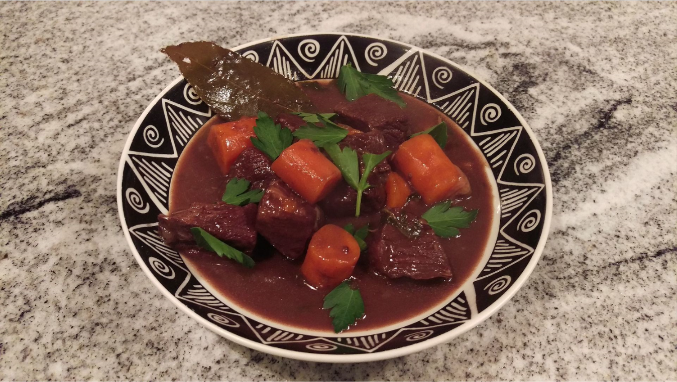 Beef bourguignon  is a beef stew braised in red wine, often red Burgundy, and beef broth, generally flavored with carrots, onions, garlic, and a bouquet garni, and garnished with pearl onions, mushrooms, and bacon.