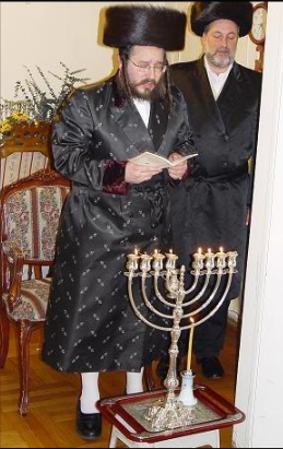 hanukkah biala rebbe lights the menorah.png