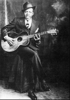 American blues singer Robert Johnson (1911 – 1938).  His landmark recordings in 1936 and 1937 display a combination of singing, guitar skills, and songwriting talent that has influenced later generations of musicians.