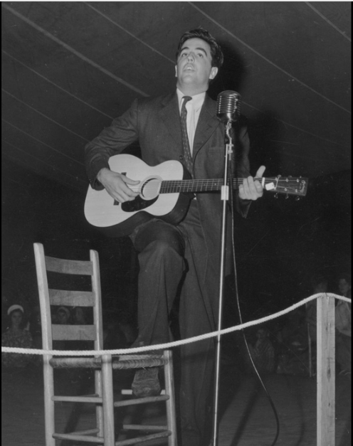 Alan Lomax playing guitar on stage at the Mountain Music Festival, Asheville, North Carolina, in the early 1940s.  Alan Lomax (January 31, 1915 – July 19, 2002) was an American ethnomusicologist, best known for his numerous field recordings of folk music of the 20th century.  He was also a musician himself, as well as a folklorist, archivist, writer, scholar, political activist, oral historian, and film-maker. Lomax produced recordings, concerts, and radio shows in the US and in England, which played an important role in preserving folk music traditions in both countries, and helped start both the American and British folk revivals of the 1940s, 1950s and early 1960s.  He collected material first with his father, folklorist and collector John A. Lomax, and later alone and with others, Lomax recorded thousands of songs and interviews for the Archive of American Folk Song, of which he was the director, at the Library of Congress on aluminum and acetate discs.