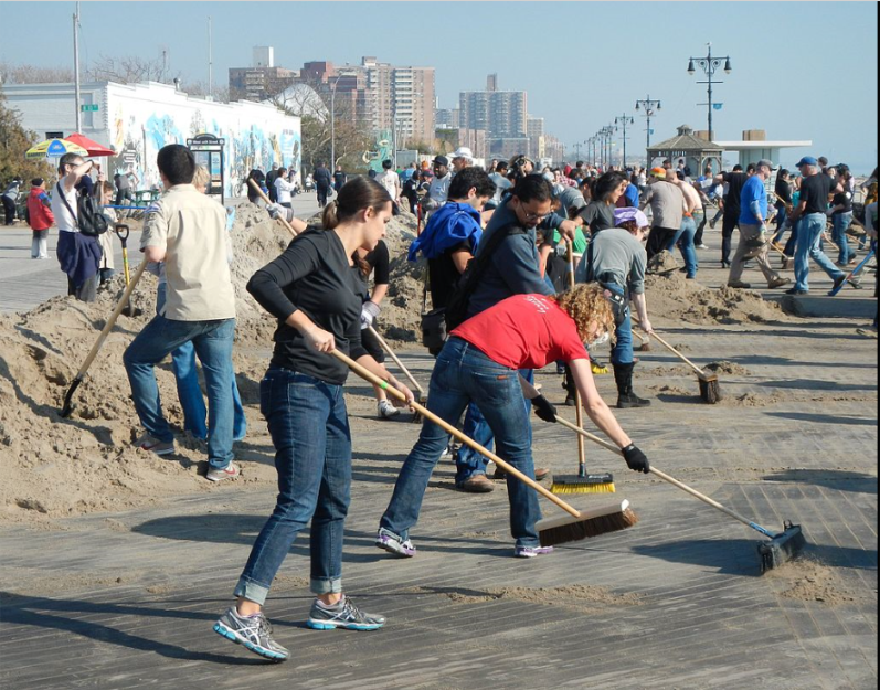 Volunteers sweep the boardwalk in Brooklyn after the 2012 Hurricane Sandy.