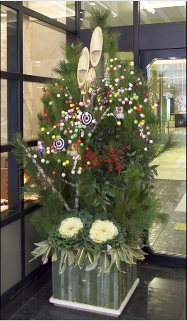 This photograph shows a  kadomatsu , a traditional decoration for the new year in  Japan . The  ikebana  arrangement includes auspicious pine, bamboo, and other felicitous symbols.