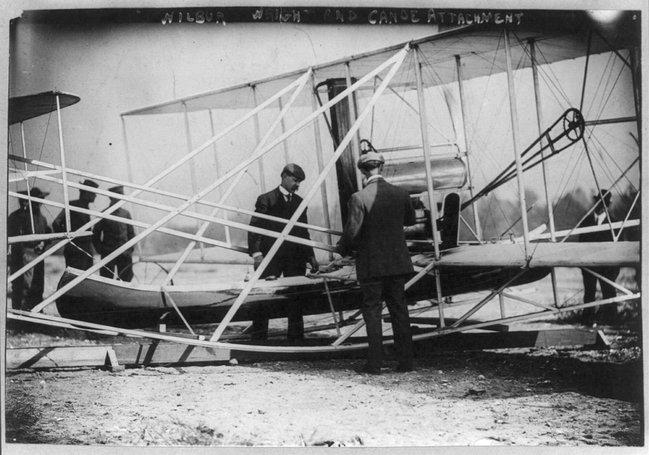 Charlie Taylor and Wilbur Wright attach a canoe onto a new Flyer at Governor's Island New York, October 1909.