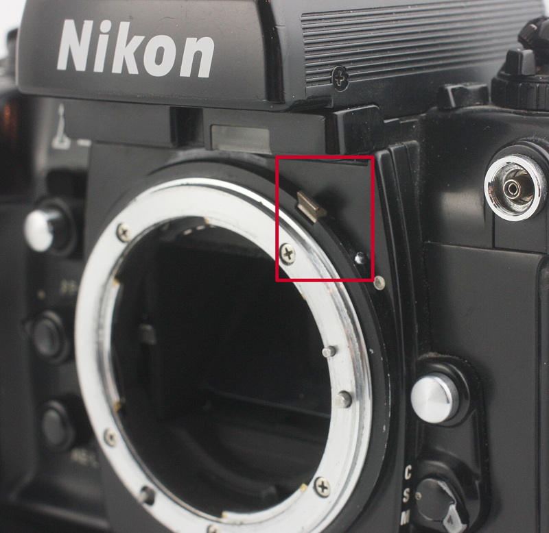Some AI Nikon bodies have the ability to flip the AI lever up and out of the way, allowing the mounting of Non-AI lenses. These levers must be unlocked by depressing the small silver button in the lower right corner of the red rectangle above.