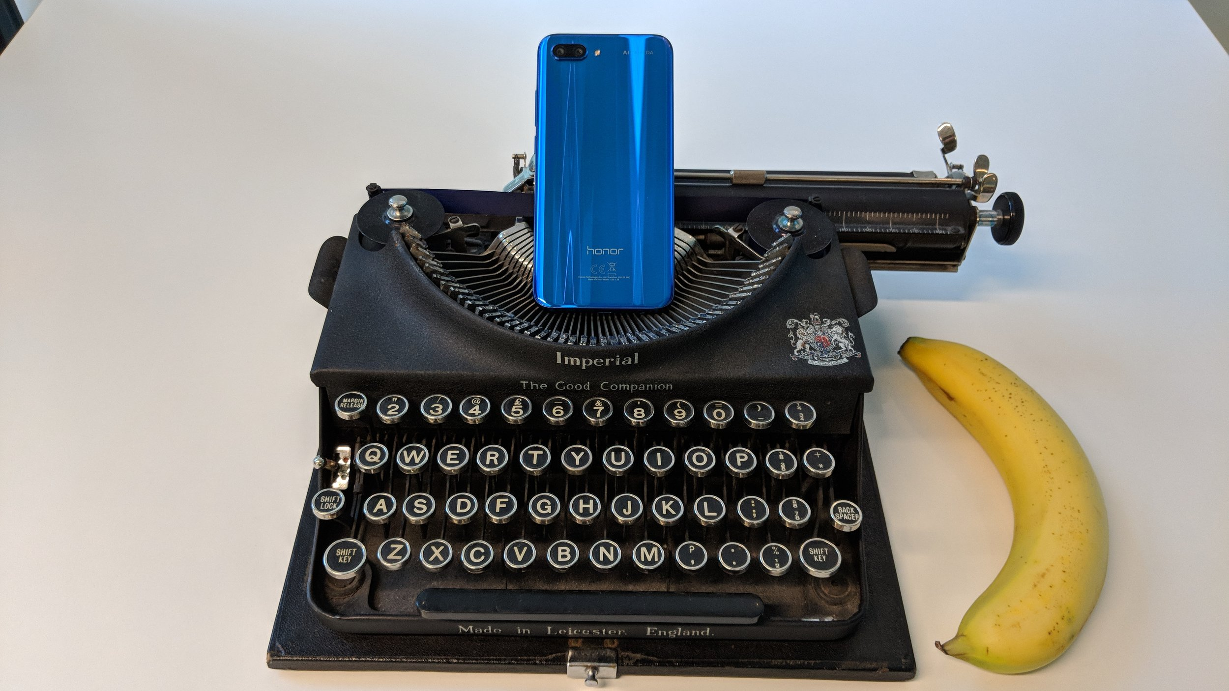 """The Honor 10 """"glass sandwich"""" with typewriter and banana for scale..."""