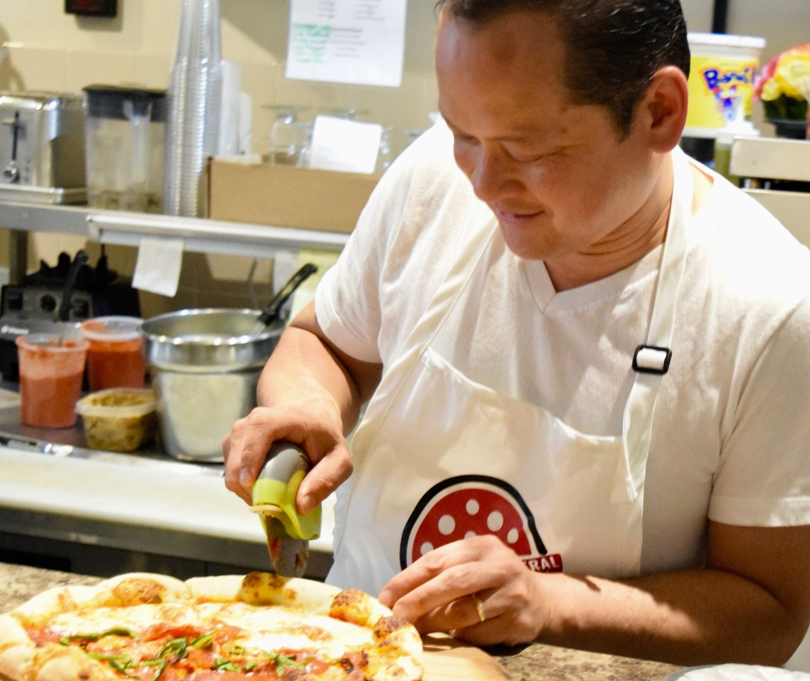 "Hòa Voscott slices a combo pizza that's just come out of the oven at Central Pizza Pies' second Pop-Up for Good. This combo is half four cheese with fresh basil and half ""3P"" – Pepperoni, Poblano and Parmesan.  Photo from Central Pizza Pie"