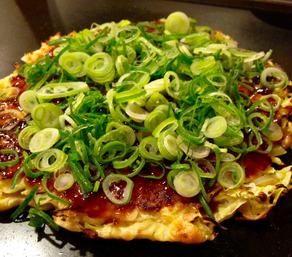 """A few evenings later, Jade and I had the enjoyable experience of trying Okonomiyaki. Translated to """"Grilled any way you like"""", this is a cross between an omelet and a pancake. The filling can be left up to the imagination but usually consists cabbage, egg and flour with a protein of seafood or pork. The fun part is that you can cook the pancake yourself over a large flat griddle in the middle of the table. Jade and I had a great evening enjoying views of the river while we sipped on sake and cut off wedges of our seafood combination Okonomiyaki. The seafood was tender and the eggs were fluffy, each bite complimented by a hefty dose of scallion. The grill kept the meal hot throughout our entire dinner and I was in heaven experimenting with all of the condiments at my disposal."""