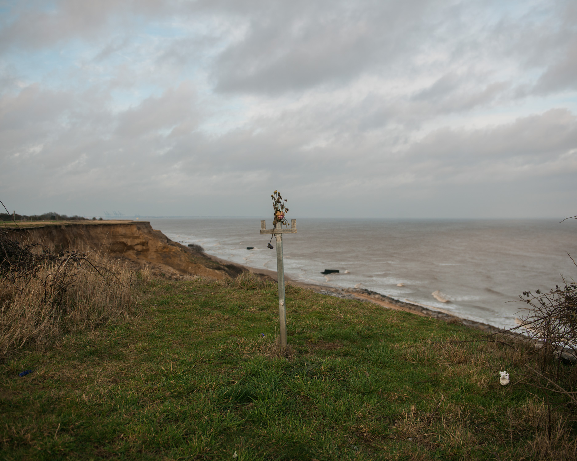 The last remaining railing of the steps that used to lead down to the beach near Hopton, Suffolk, memorialised with plastic flowers.