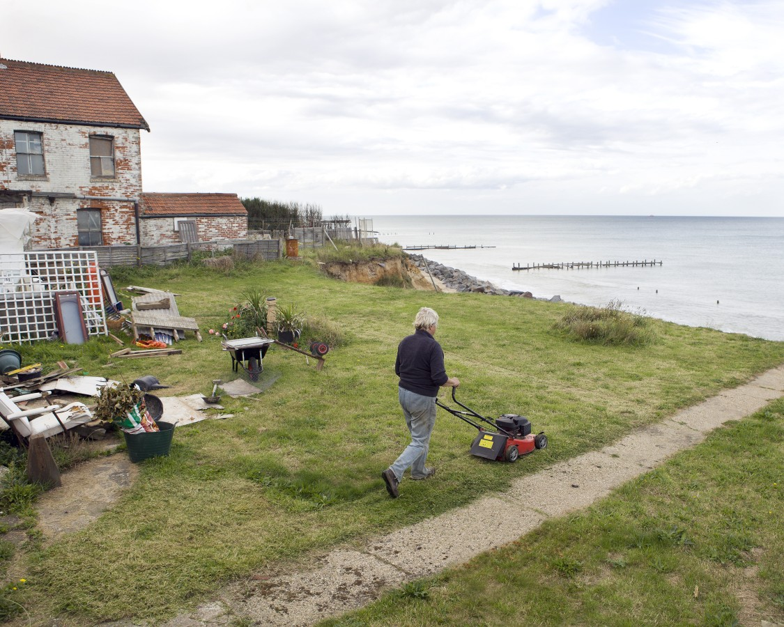 """Happisburgh, Norfolk, is one of the hardest hit communities on the east coast. The government has relocated nearly all the residents from the sea front houses. In this picture Bryony Nierop-Reading, one of the only few remaining residents, mows the lawn of the bungalow she refuses to leave. """"Why should I be made to move from the home I love? I think it would be totally immoral for me to take any money at all for it."""""""