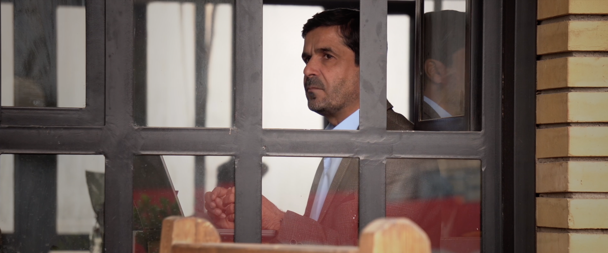 Journalist Ali Maula looks in the distance from restaurant window.png