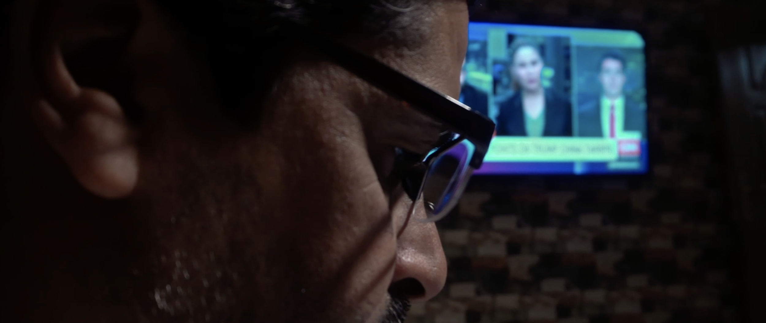 Journalist Ali Maula works on his laptop while news display on TV screen.png