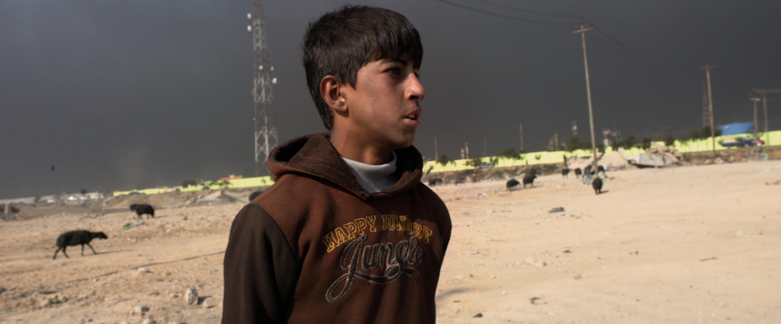 Shepherd boy talks to journalist Ali Maula under smoky sky.png