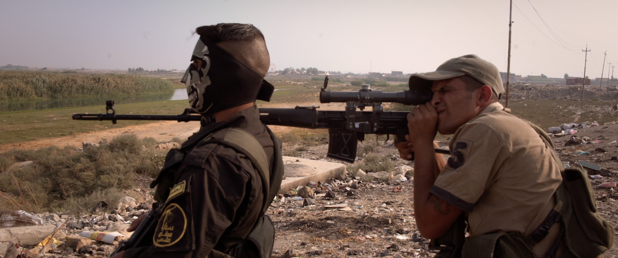 Soldier pointing rifle next to masked soldier.png