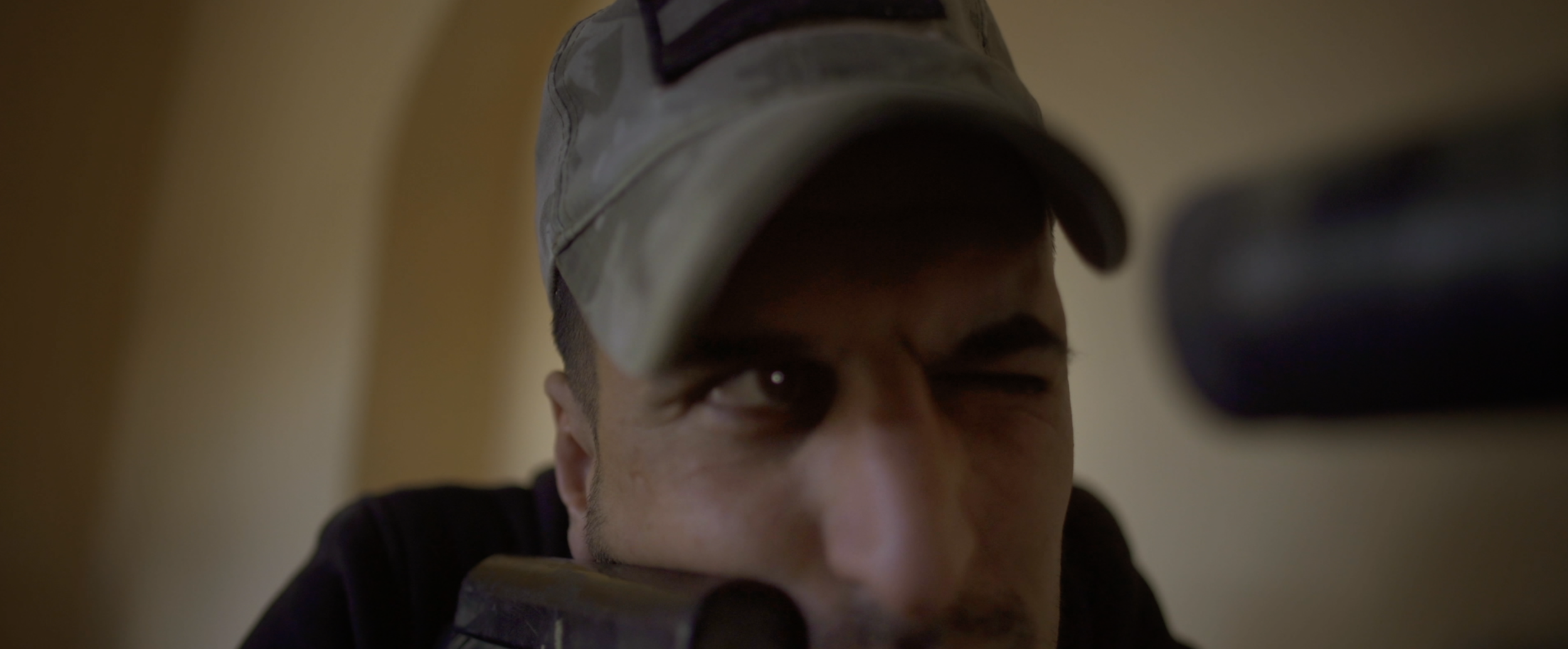Soldier pointing rifle, looking through peephole.png