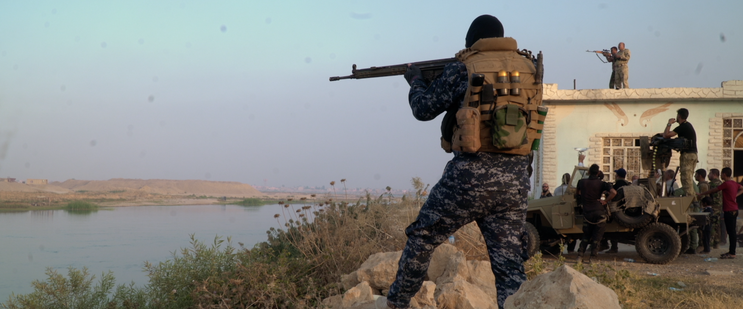 Soldiers points rifle overlooking Tigris river.png