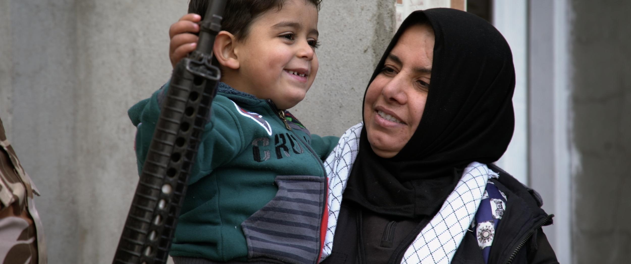 Um Hanadi holding grandson .png