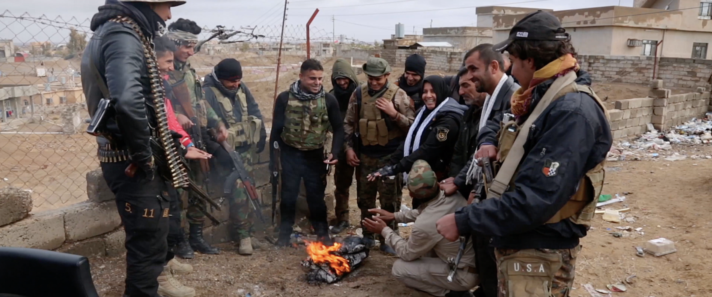 Um Hanadi and her soldiers around small wood fire.png