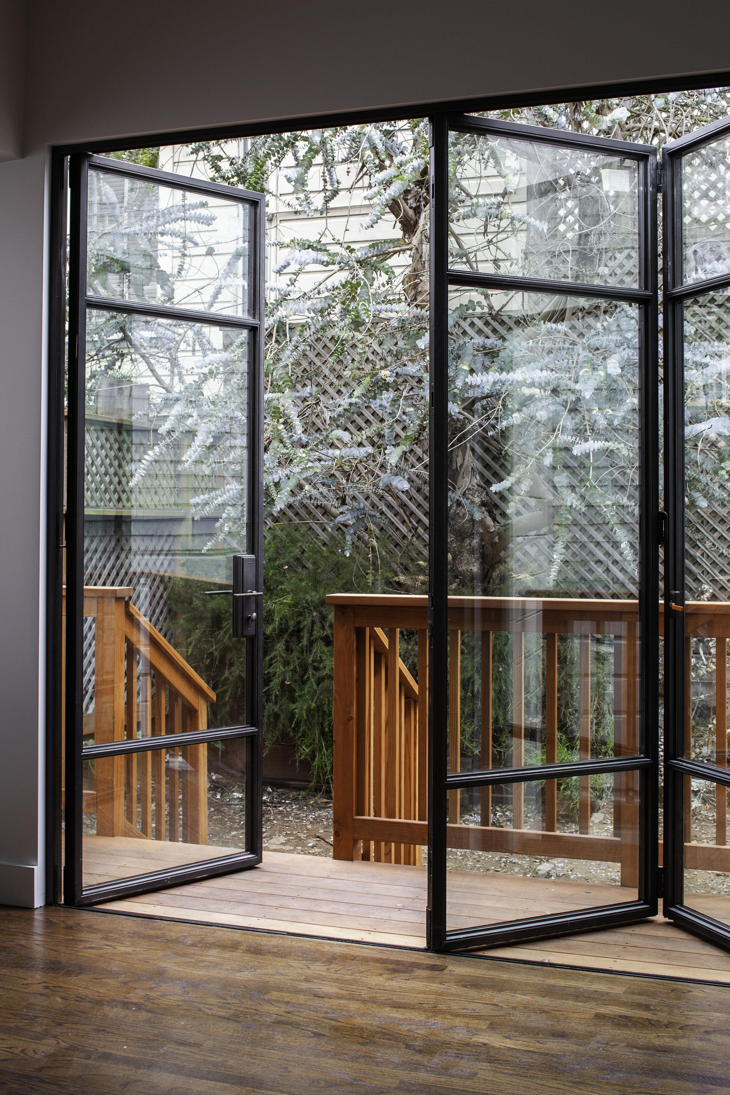 Steel-framed bi-folding doors allow light to flood the kitchen.