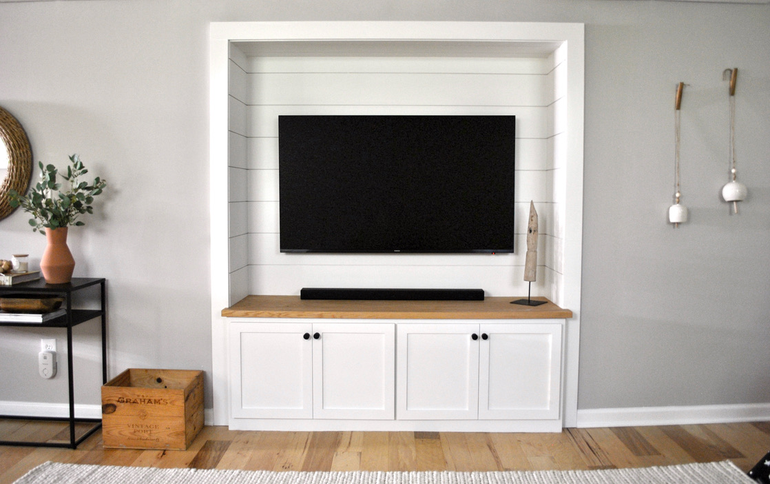 Basement built in with shiplap paneling, white shaker cabinetry, and matte black hardware perfect for a big tv and lots of toy storage below.