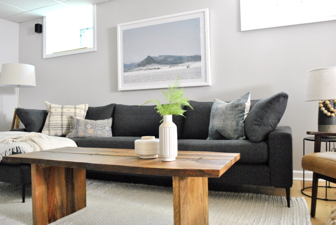 A large sleek sofa with live edge table and leather chair make for the perfect family basement space.
