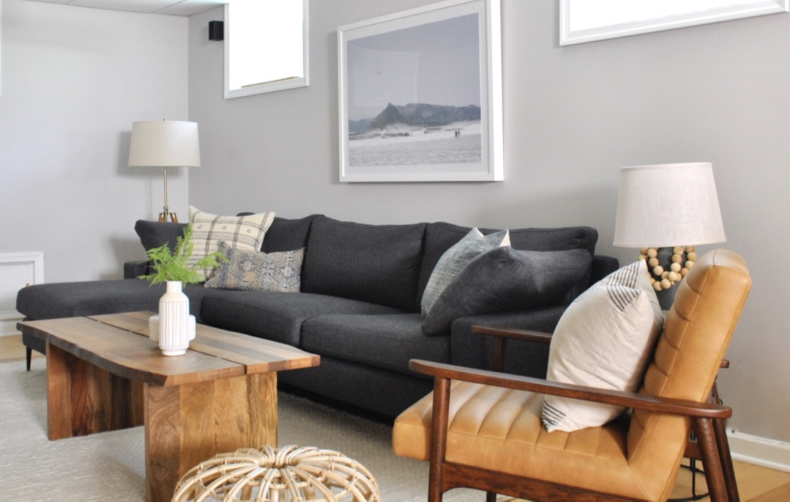 Basement Family room with dark sofa and mid-century leather chair.