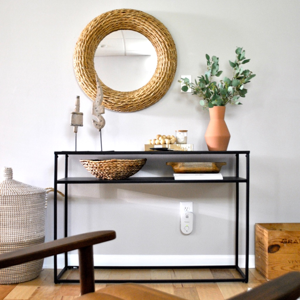 Sleek metal console table with wood an organic accents.
