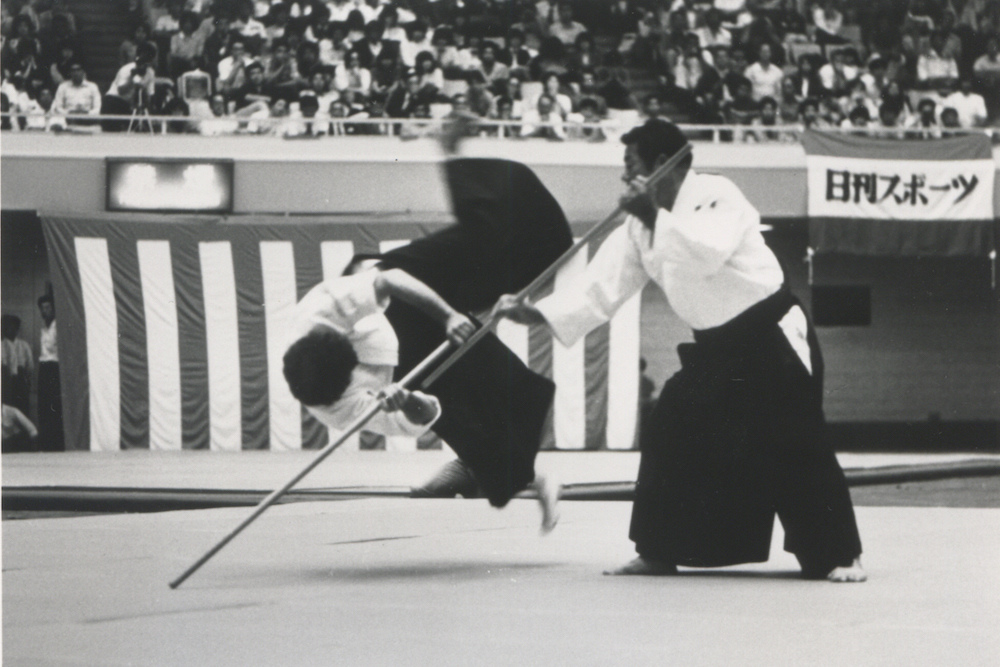 A young Rob takes a high fall from Saito Shihan's staff controlling technique the 1981 Aikido demonstration in Tokyo's famous Nippon Budokan stadium.